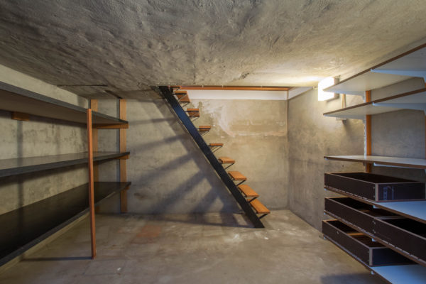 empty basement in abandoned old industrial building with little light and a wooden stairs and cement walls
